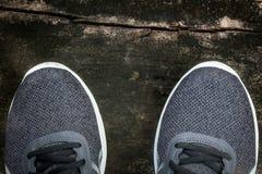 Graue Laufschuhe auf einem grungy Bretterboden Stockfotografie