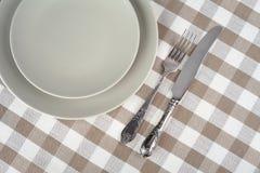 Graue leere Platte mit Weinlesegabel und Messer auf beige karierter Tischdecke Lizenzfreies Stockfoto