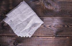 Graue Leinenserviette auf einem braunen hölzernen Hintergrund Lizenzfreies Stockbild