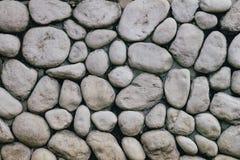 Graue oder graue Steinwand mit rundem Stein der natürlichen Beschaffenheit Im altem Stil Wand des Natursteins Stockfotografie