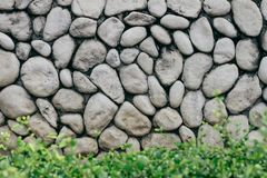 Graue oder graue Steinwand mit rundem Stein der natürlichen Beschaffenheit mit niedrigem Busch in der Front Im altem Stil Wand de Stockfoto