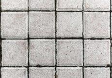 Graue Pflasterungsplatten oder -steine des Betons oder des Kopfsteins Lizenzfreies Stockfoto