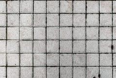 Graue Pflasterungsplatten oder -steine des Betons oder des Kopfsteins Lizenzfreie Stockfotos