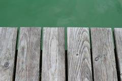 Graue Planke über grünem Wasser Stockbilder