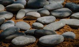Graue, Poliersteinkiesel auf dem Sand stockbild
