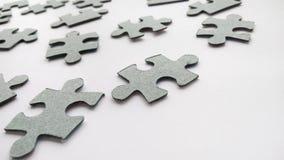 Graue Puzzlestücke der Zusammenfassung auf weißem Hintergrund stockfoto