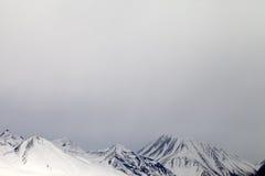 Graue schneebedeckte Berge im Nebel Lizenzfreies Stockbild