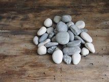 Graue Steine auf einem Holztisch Lizenzfreie Stockbilder