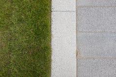 Graue Steinpflasterung u. Bordstein neben Rasen des grünen Grases lizenzfreies stockbild