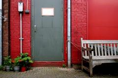 Graue Tür auf roter Wand stockbilder