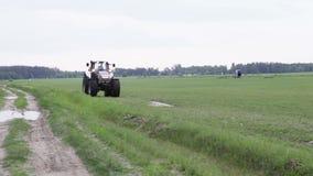 Graue Traktorfahrten auf das grüne Feld stock footage