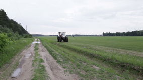 Graue Traktorfahrten auf das grüne Feld stock video