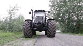 Graue Traktorfahrten auf das grüne Feld stock video footage