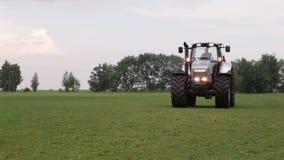 Graue Traktorfahrten auf grünes Feld stock video footage