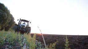 Graue Traktorfahrten auf grünes Feld stock footage