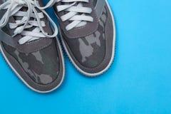 Graue Turnschuhe auf einem blauen Hintergrund lizenzfreie stockfotografie