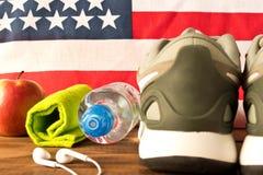 Graue Turnschuhe und Eignungszus?tze auf dem Hintergrund der amerikanischen Flagge Das Konzept der Gesundheit der Nation vorgew?h stockfoto