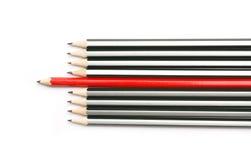 Graue und rote Bleistifte zeigen nach links stockbilder
