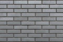 Graue Wand mit Klinkerziegelsteinen Stockfotos