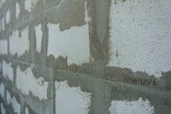 Graue Wand von Schaumblöcken auf klebriger Lösung stockfoto