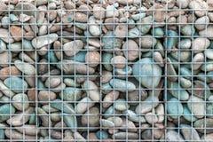 Graue weiße und blaue runde Steine im Metallmaschenhintergrund Natürliches materielles umweltsmäßigc$fechten stockbild