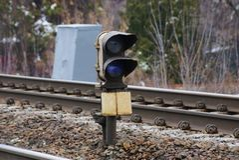 Graueisensignallampe steht unter Schiene und Lagerschwellen auf der Eisenbahn lizenzfreie stockfotos