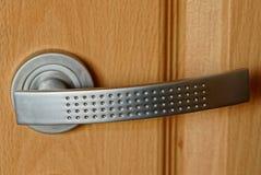 Graueisentürgriff auf einer braunen Holztür lizenzfreies stockbild
