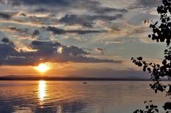 Grauer Abendhimmel über dem See, orange Sonne Stockbilder