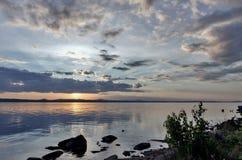 Grauer Abendhimmel über dem See, orange Sonne Stockfotografie