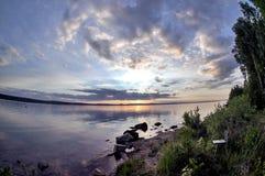 Grauer Abendhimmel über dem See, orange Sonne, Türspion Lizenzfreie Stockfotos