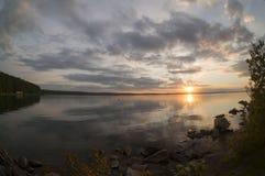 Grauer Abendhimmel über dem See, orange Sonne, Türspion Stockbild