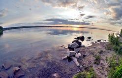 Grauer Abendhimmel über dem See, orange Sonne, Türspion Lizenzfreies Stockbild