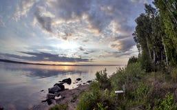 Grauer Abendhimmel über dem See, orange Sonne, Türspion Stockfotografie