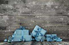 Grauer hölzerner Weihnachtshintergrund mit einem Stapel Geschenken in Blauem Stockfoto