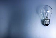 Grauer Hintergrund mit einer Glühlampe lizenzfreies stockfoto