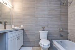 Grauer Innenraum eines neuen Badezimmers im Appartementkomplex stockbild
