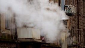 Grauer Kamin mit weißem Rauche gegen den Gebäudehintergrund mit Balkonen und Fenstern 50 fps stock footage