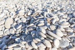 Grauer Kiesel mit blauen Schatten auf einer Seeküste Stockfotos