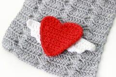 Grauer Schal mit rotem gewirktem Herzen stockbilder
