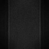 Grauer Segeltuchhintergrund auf schwarzem Leder Stockfotos