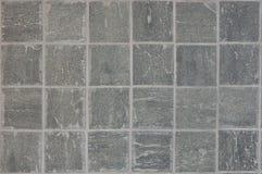 Grauer Stein deckt Hintergrund mit Ziegeln Stockfotos