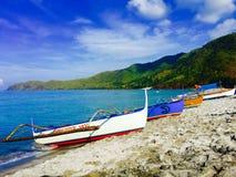 Grauer Strand und die vier Boote Stockbild