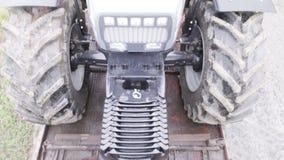 Grauer Traktor zieht in den Plattformwagen stock footage