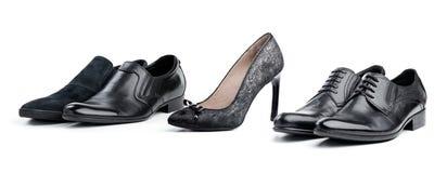 Grauer weiblicher Schuh zwischen schwarzen männlichen Schuhen Lizenzfreie Stockfotos