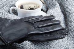 Grauer Wollschal und -Lederhandschuhe um die weiße Schale von coffe Stockfotos