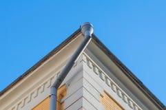 Graues Abflussrohr auf der Ecke des Gebäudes Lizenzfreies Stockfoto