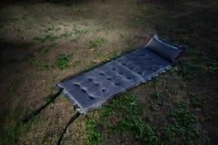 Graues aufblasbares kampierendes Bett auf dem Boden in der Nacht Kampieren in der Dunkelheit stockfotografie