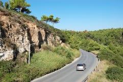 Graues Auto auf einer Straße umgeben durch malerische grüne Vegetation, G stockbilder