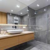Graues Badezimmer mit langem Countertop lizenzfreies stockbild