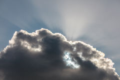 Graues cloudscape mit der Sonne, die hinter ihr scheint Stockfotografie